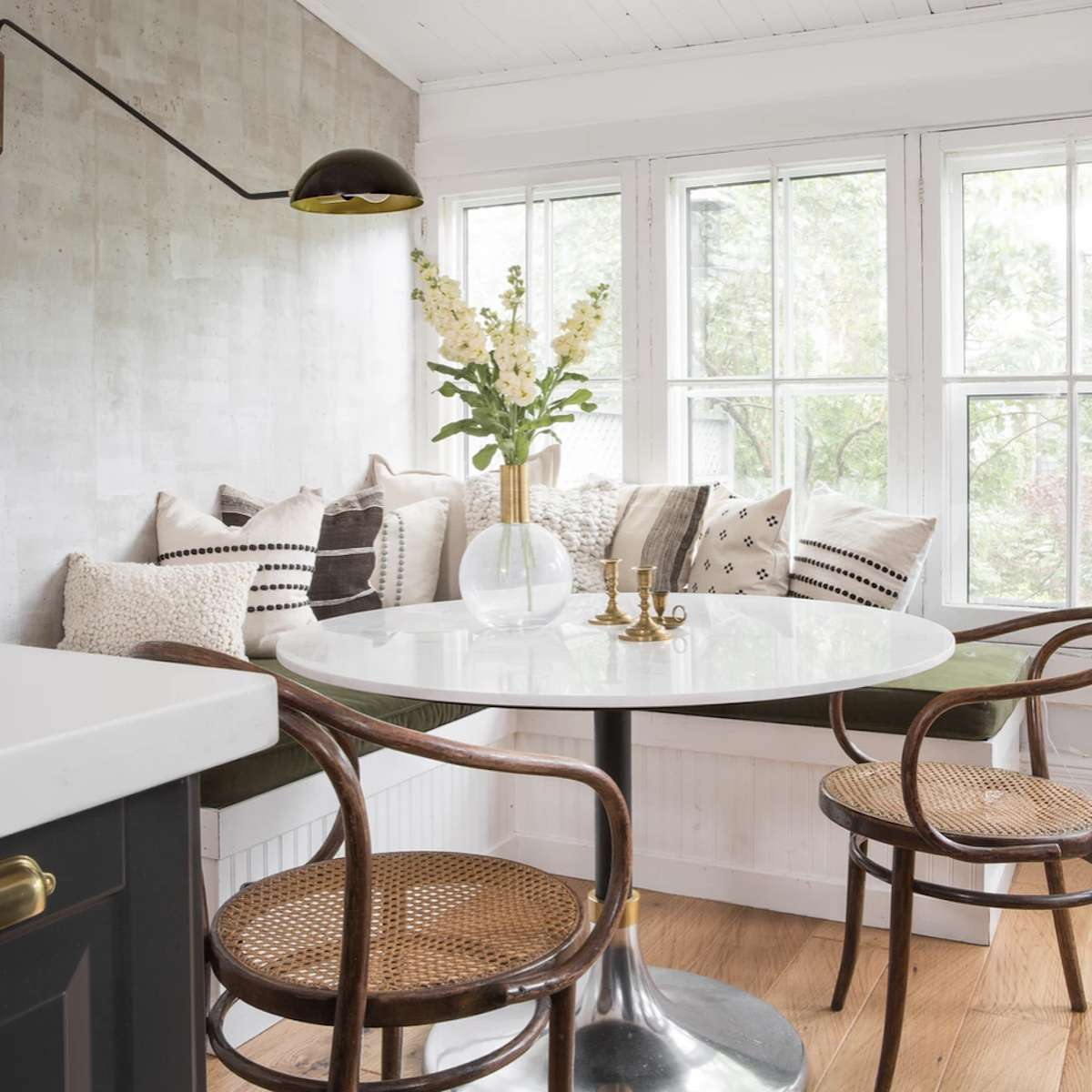 breakfast nook in kitchen with green cushions and white table