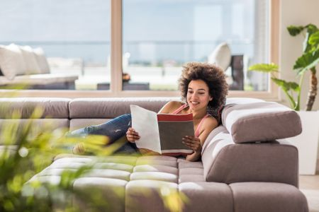 Hy African American Woman Relaxing On Sofa In The Living Room And Reading A Magazine Skynesher Getty Images Home Decor Catalogs