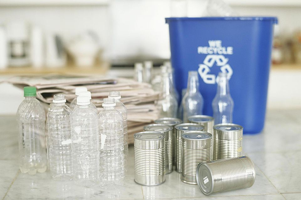 Recycling bin, empty plastic bottles and cans on table