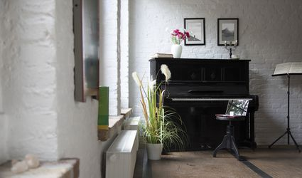 Piano with laptop on a stool in comfortable loft apartment