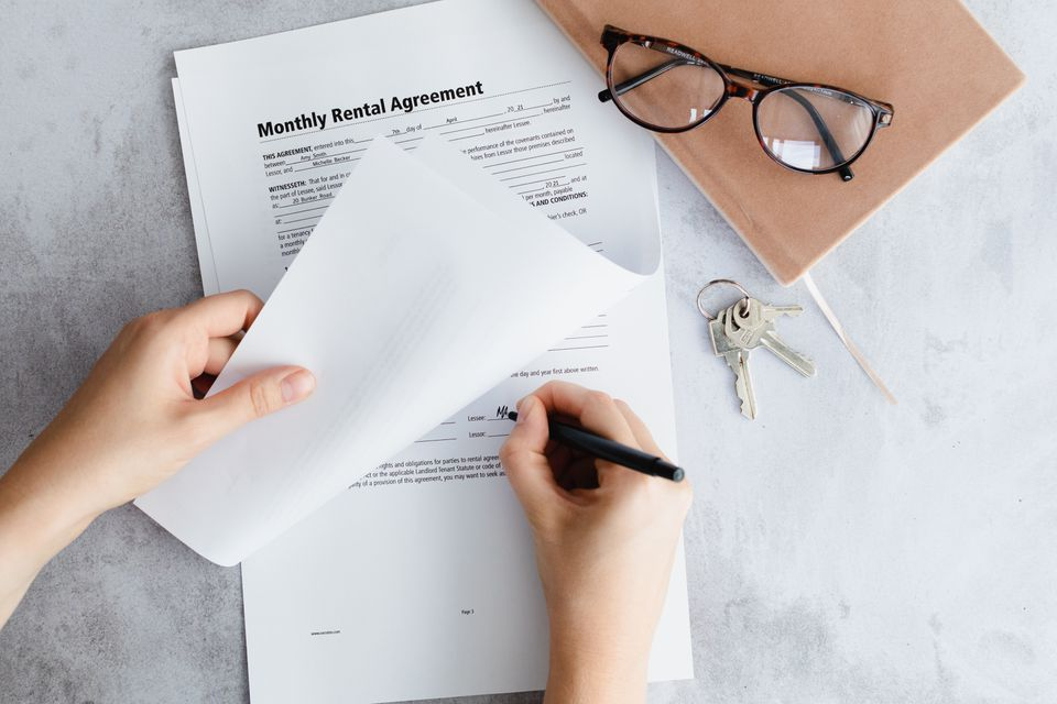 Apartment lease documents signed by hand next to brown notebook, glasses and keys