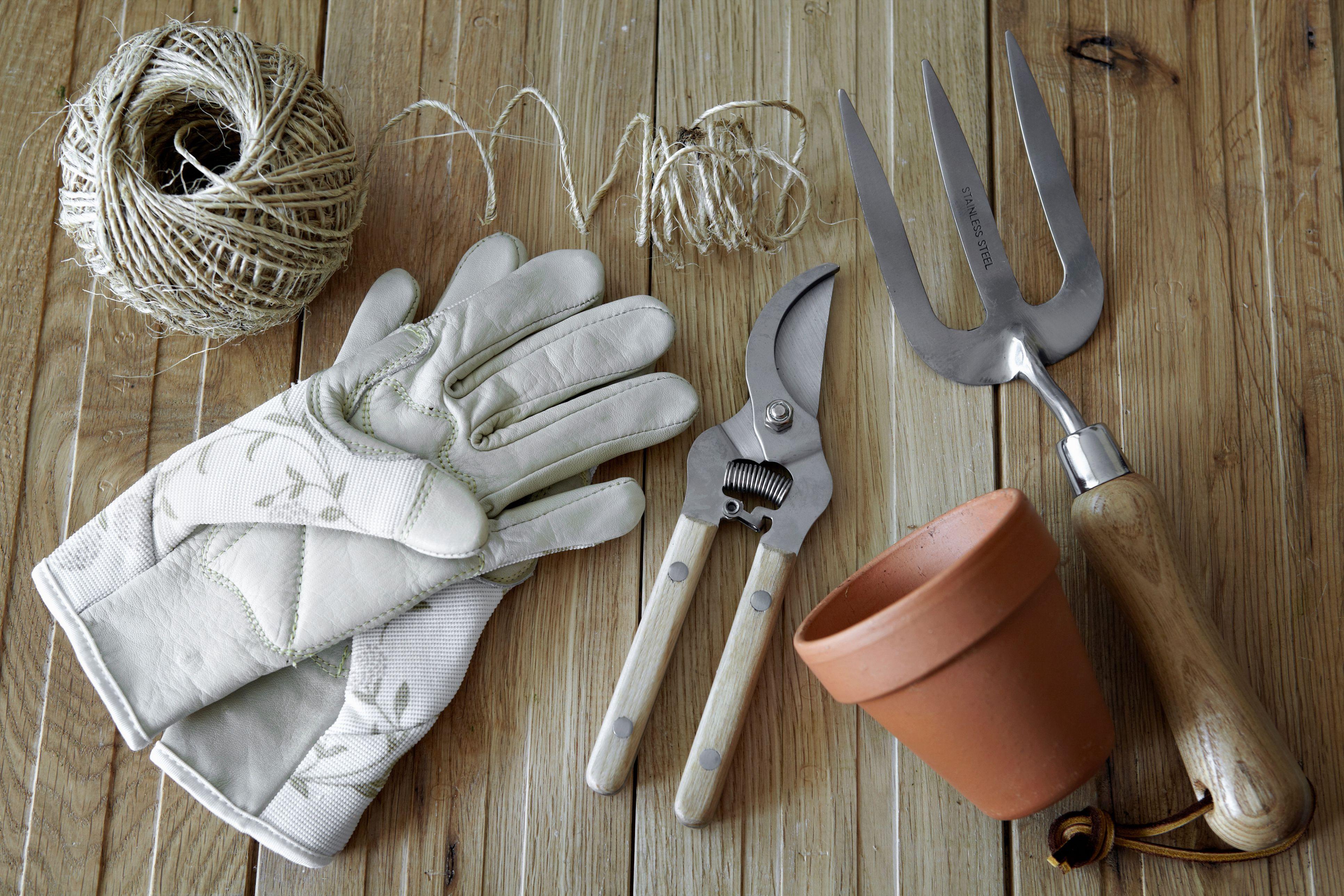 Guantes de jardinería, podadoras, macetas y cordeles sobre una mesa .