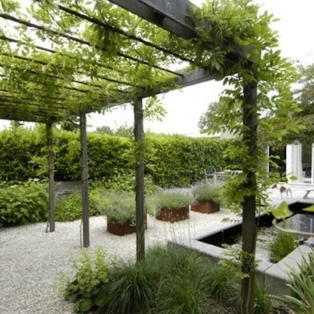arbor and square planters on gravel patio area