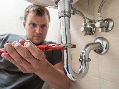a plumber holding a wrench on a pipe under a sink