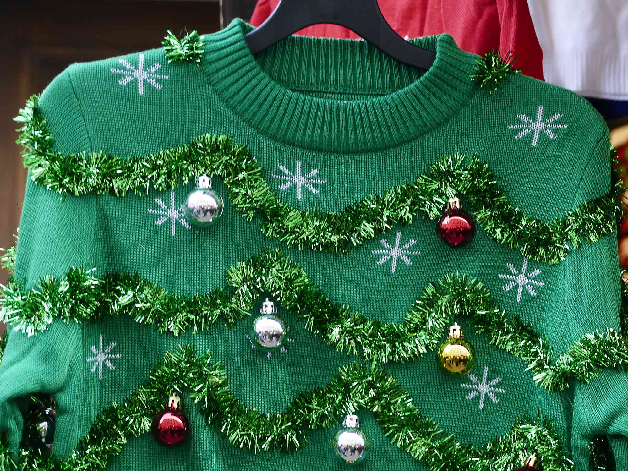 Beautiful or ugly: green Christmas sweater with decor balls