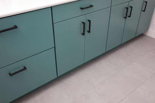 Green cabinets above new tile flooring