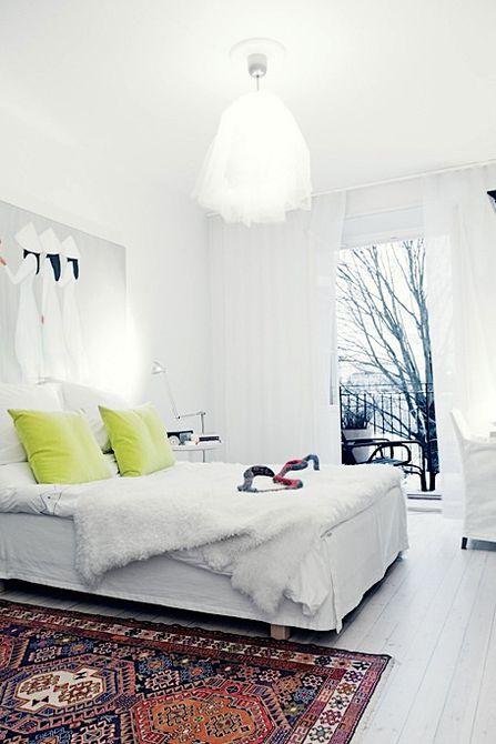 Habitación totalmente blanca con una alfombra escandinava de colores brillantes