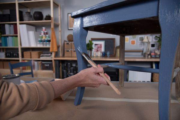 Woman painting a chair with chalky finish paint