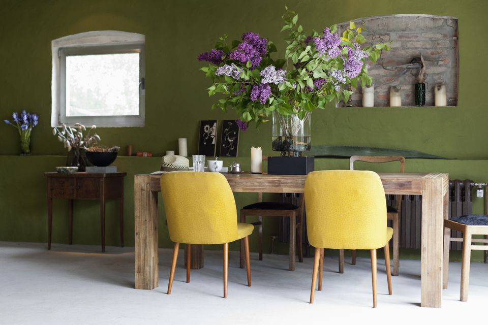 Dining room with yellow chairs and wooden table with huge arrangement of flowers