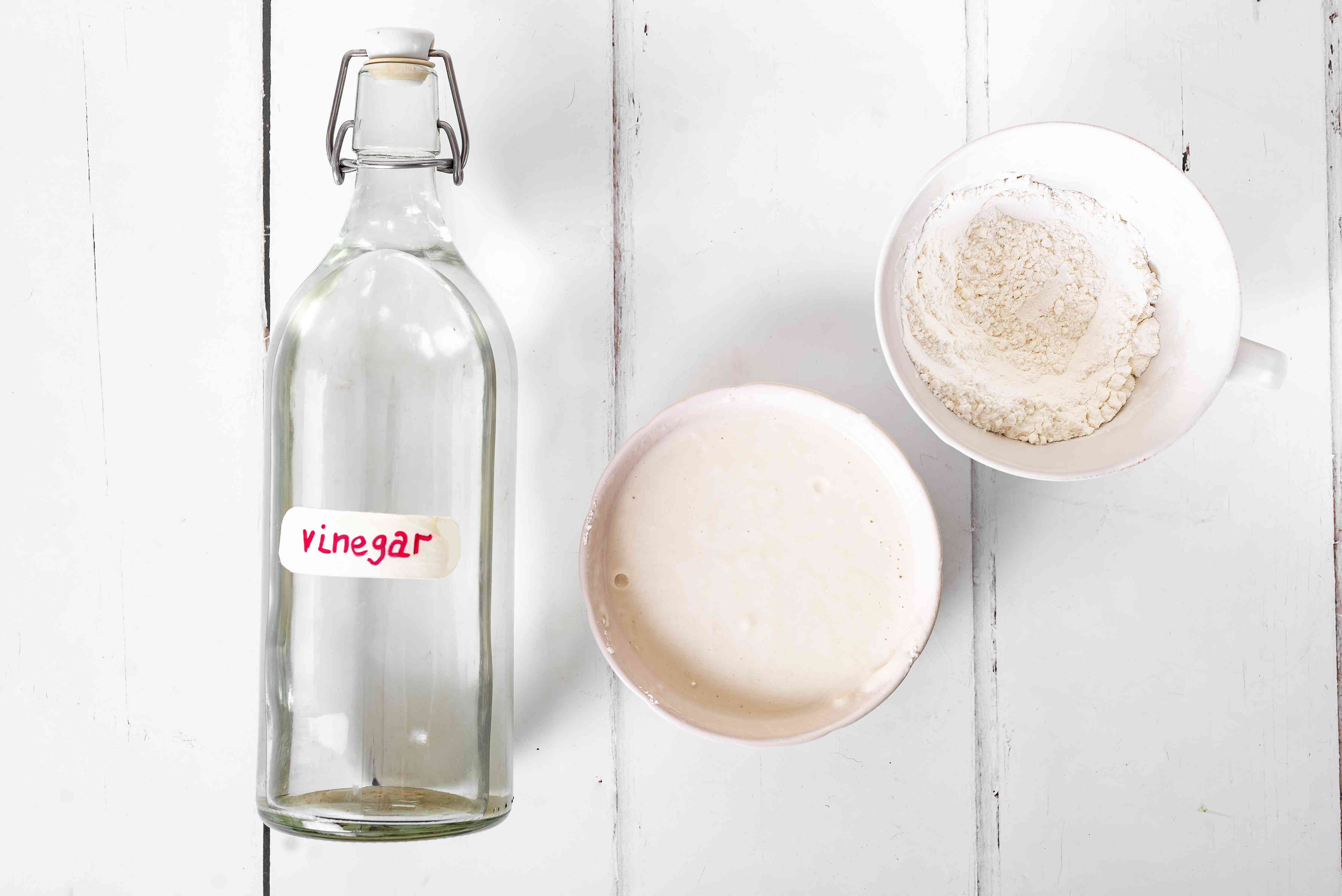 White vinegar in glass bottle next to cup of all-purpose flour to make past in middle