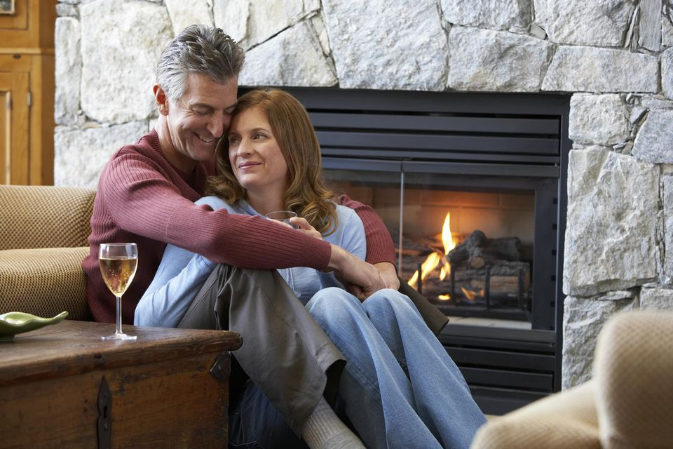 Mature couple sitting near fireplace, embracing, drinking wine
