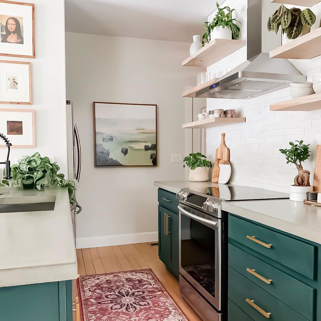 Kitchen with green cabinets and red rug