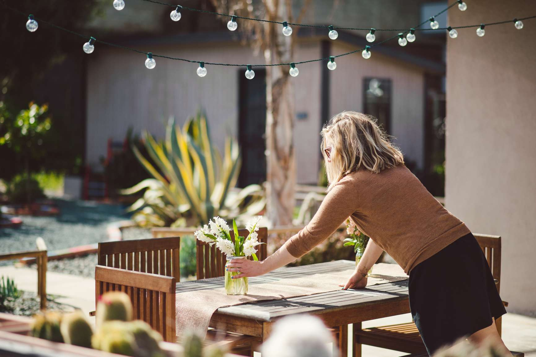 Woman placing plant on outside table with strand of hanging lights above..