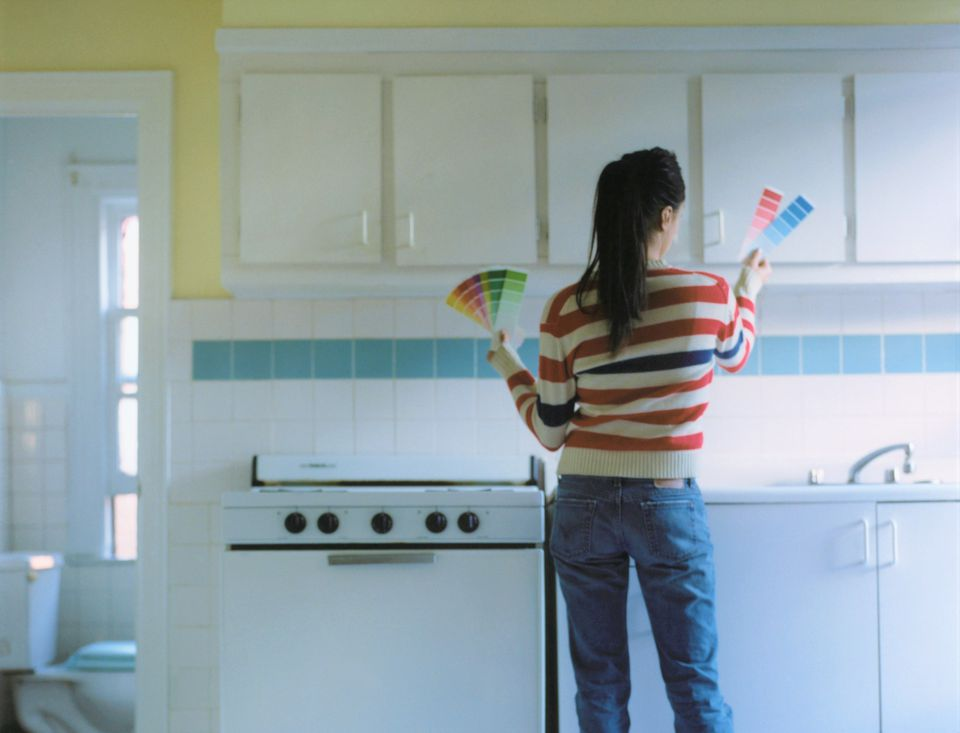 Woman looking at paint swatches in kitchen