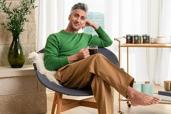 Tan France poses in al iving room next to a bar cart with Starbucks coffee. He's holding a clear mug of coffee and wearing a green sweater and camel pants