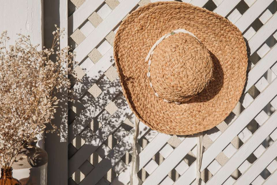 straw hat hanging on a trellis