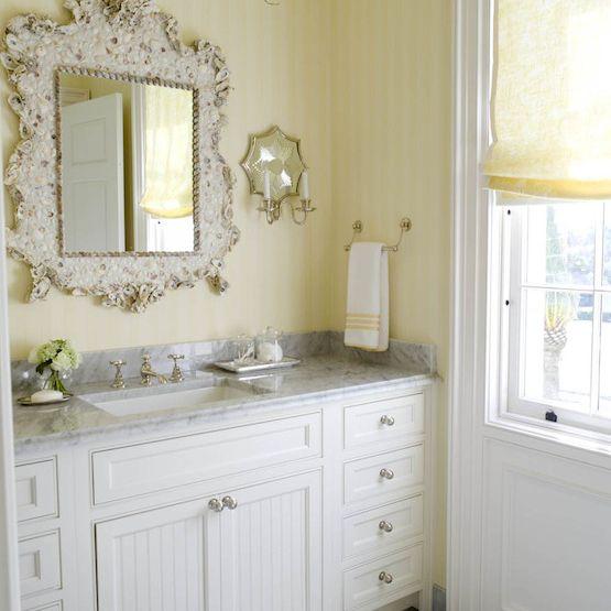 A beadboard bathroom vanity with yellow wallpaper