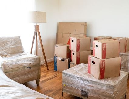 Moving boxes and wrapped furniture in light-filled apartment