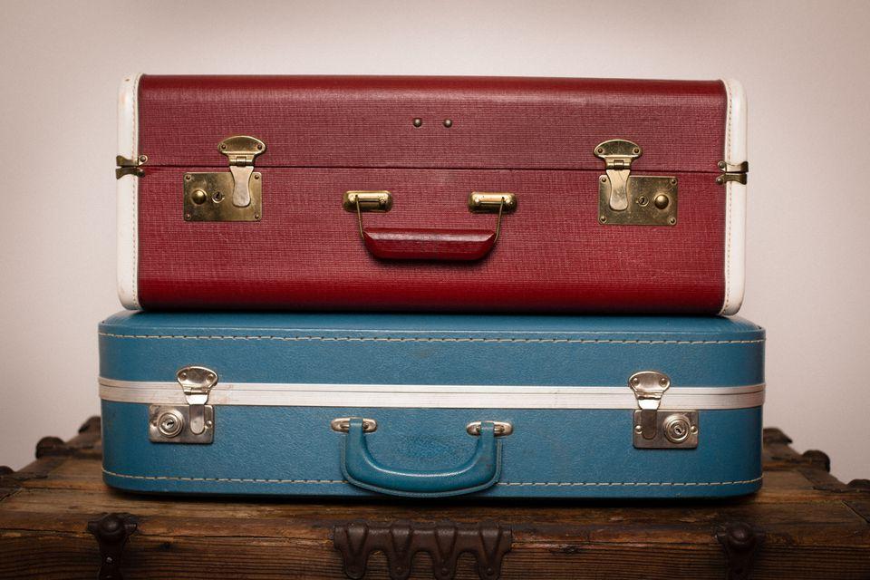 Dos maletas retro apiladas sobre baúl de madera