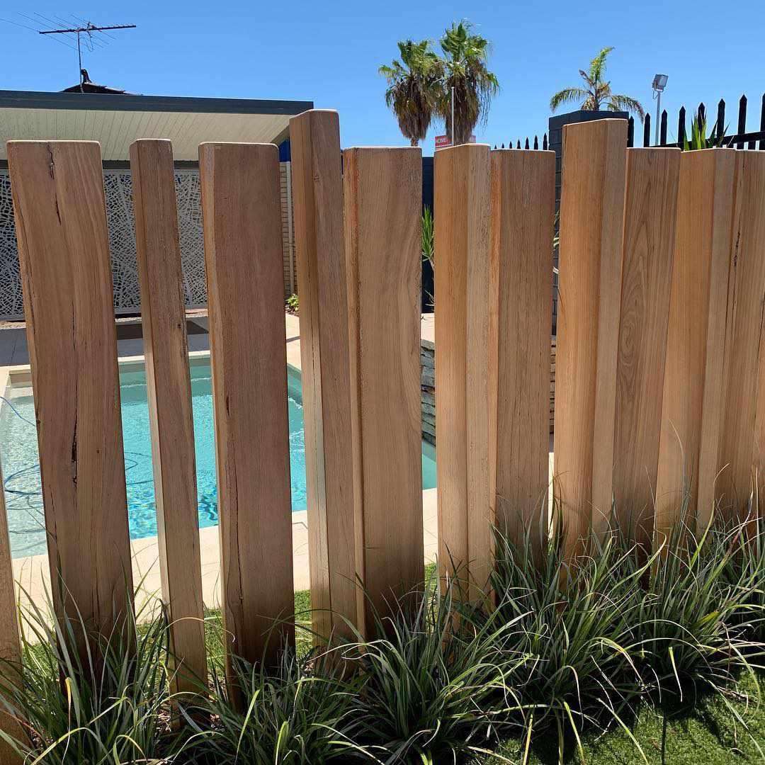 Wood posts surrounding a backyard pool.
