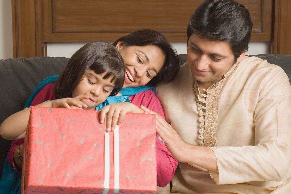Close-up of a couple and their daughter sitting on a couch with a gift
