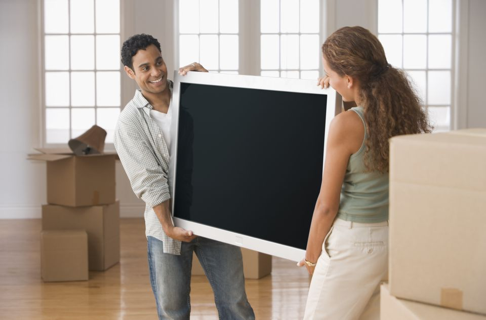 Hispanic couple carrying television