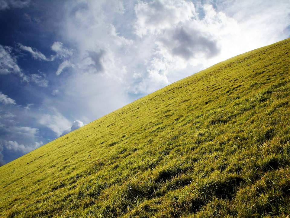 half cloud sky , half grassy hill diagonally