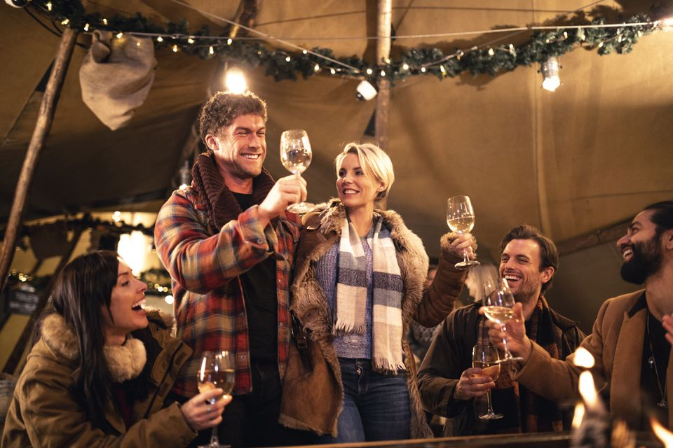 Friends making a toast in a rustic chic tent