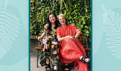 Phoebe Cheong of @WelcomeToTheJungleHome poses with her mom on a bench in front of foliage