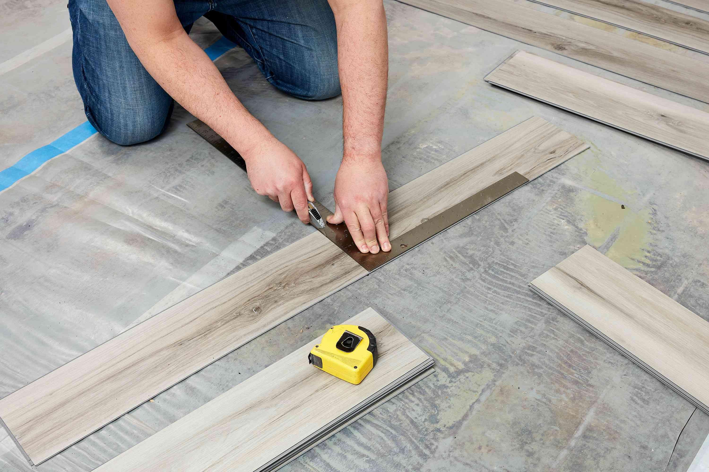 Vinyl basement flooring being measured for installation