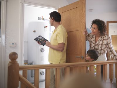 Mother and son watching father check hot water tank with energy application on digital tablet