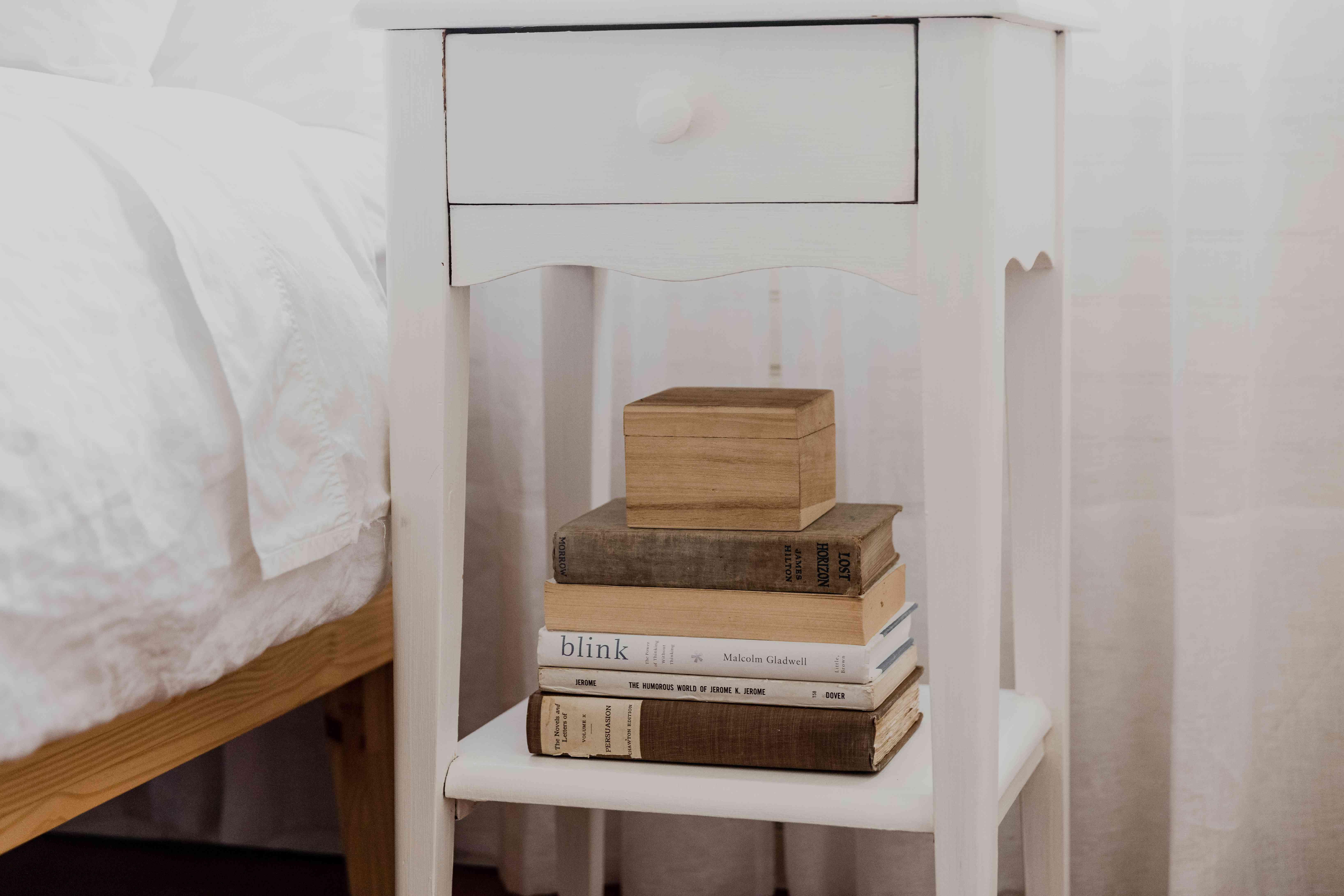Books stacked on lower shelf of nightstand with wooden box on top