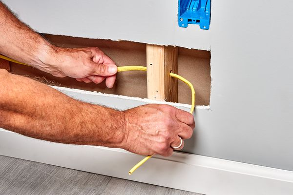 Electrical wire being run through wood beam in wall for nearby electrical box