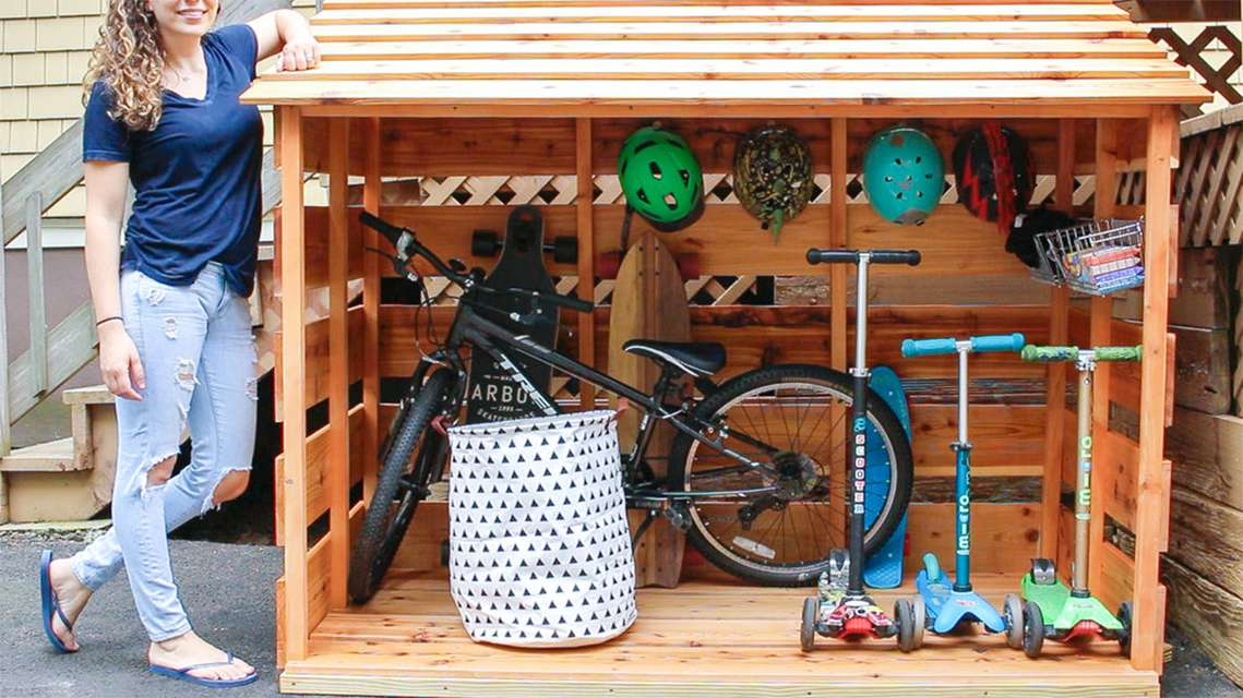 A woman standing by a shed with bikes in it
