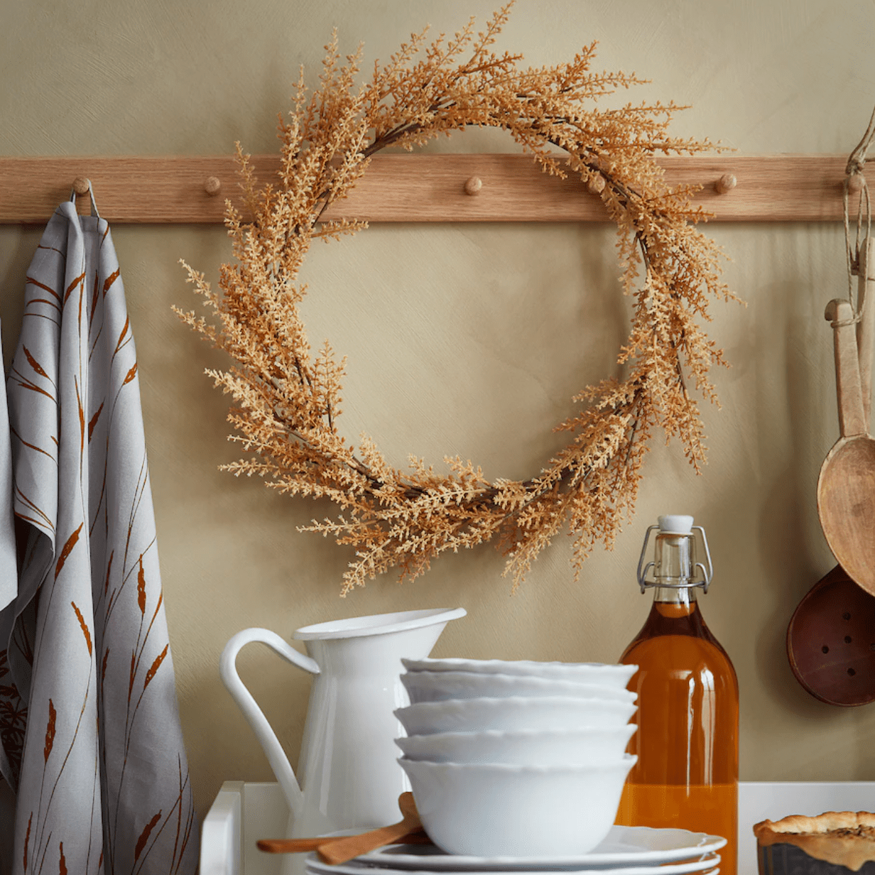 A neutral fall wreath displayed in a kitchen
