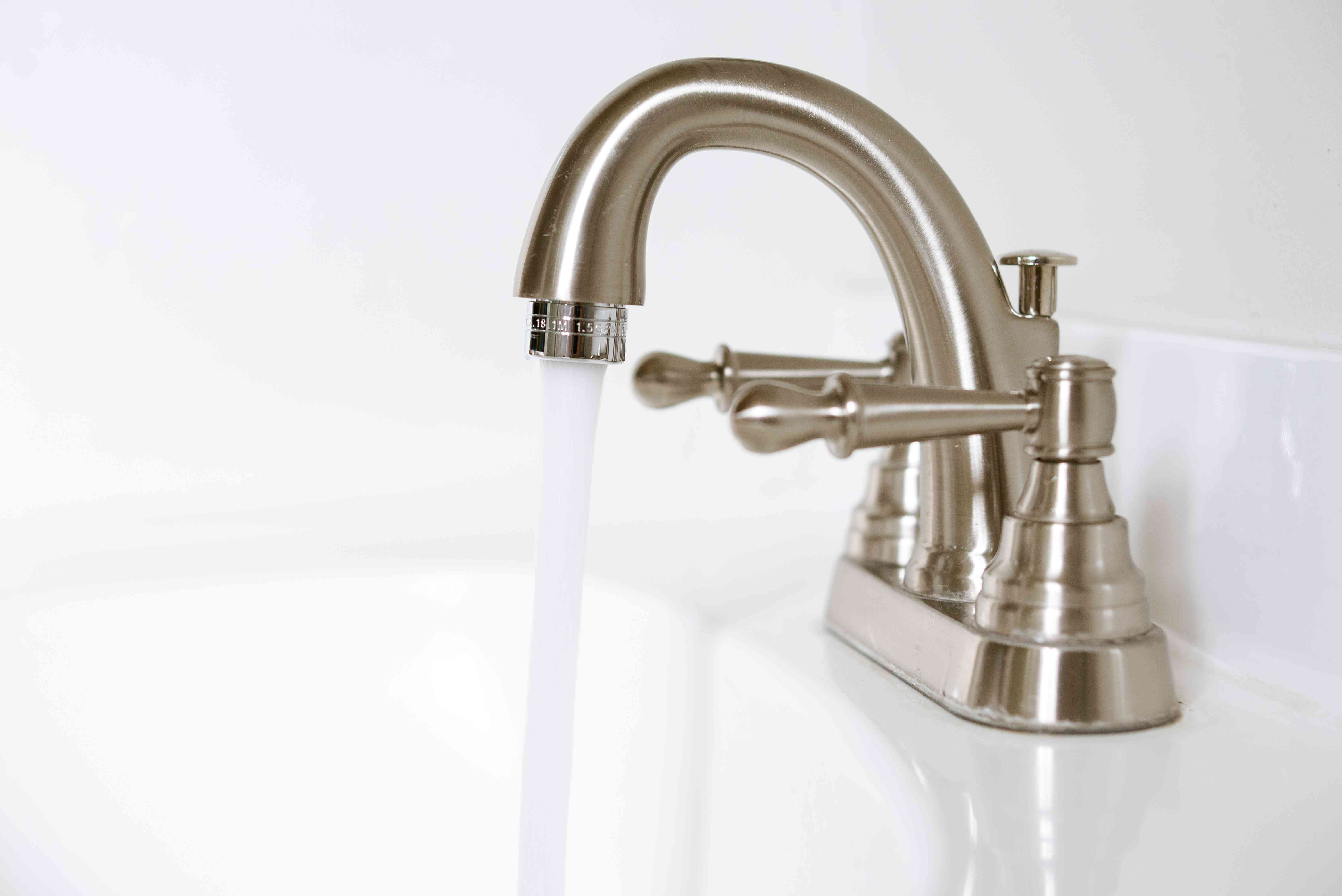 Faucet running with flowing water to test aerator