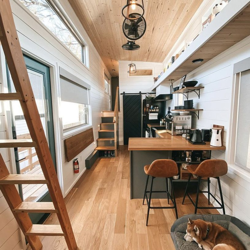 tiny home with upper ledge and dark trim/cabinets