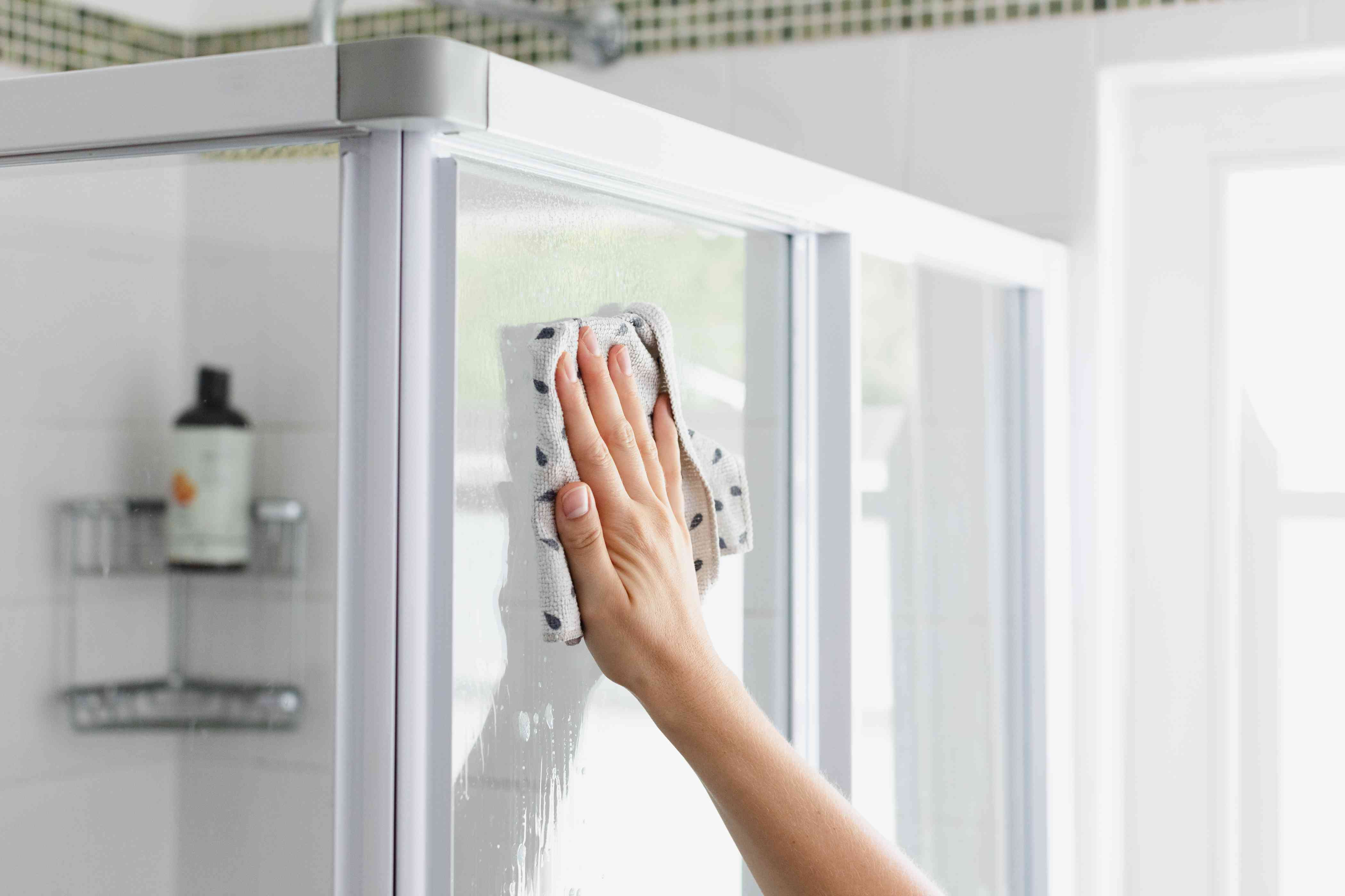 Shower glass doors wiped down with rag to reduce bathroom odors