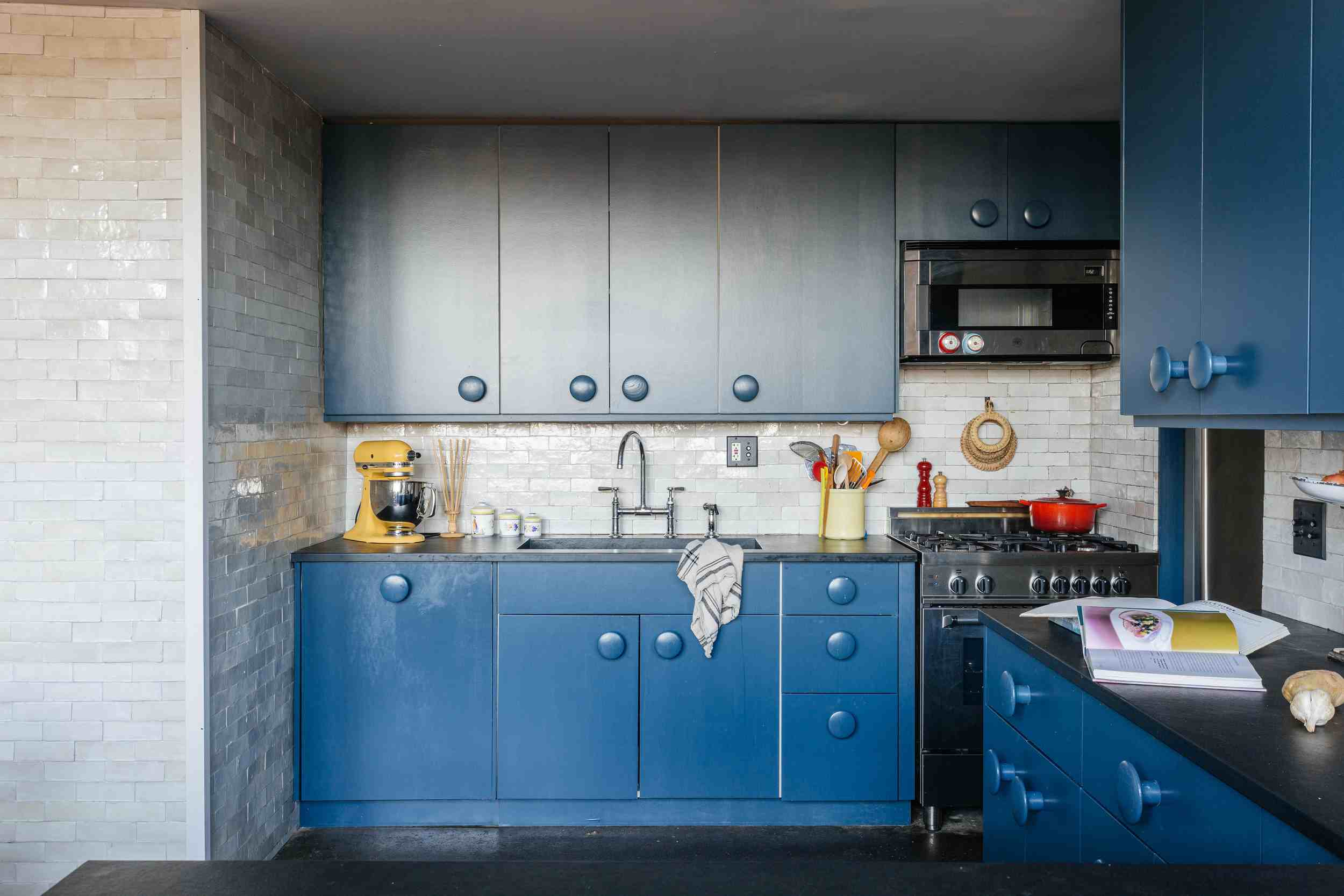 Deep blue kitchen cabinets with large, round knobs