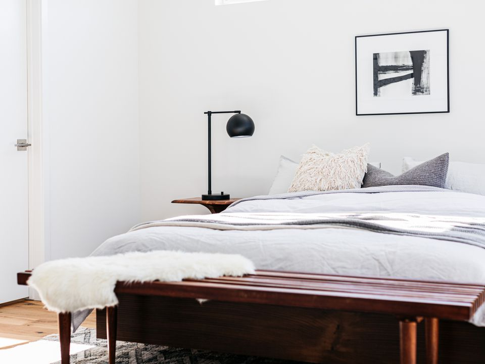 Scandinavian bedroom with white and gray sheets next to black lamp with dark brown wood bench in front