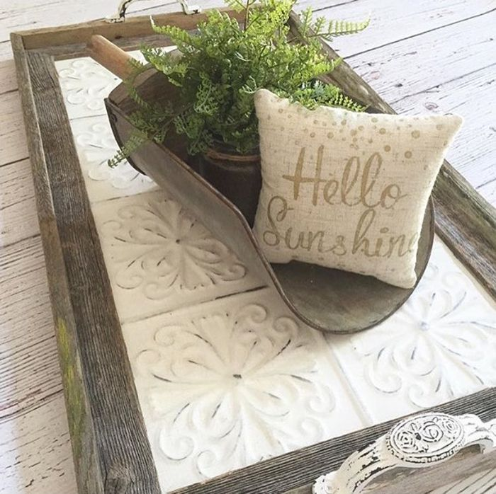 Vingtage tile used as a tray with planter and pillow atop.
