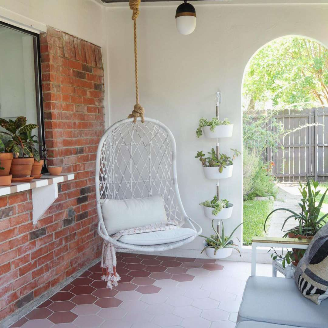 A swing chair hanging in the corner of an outdoor room.