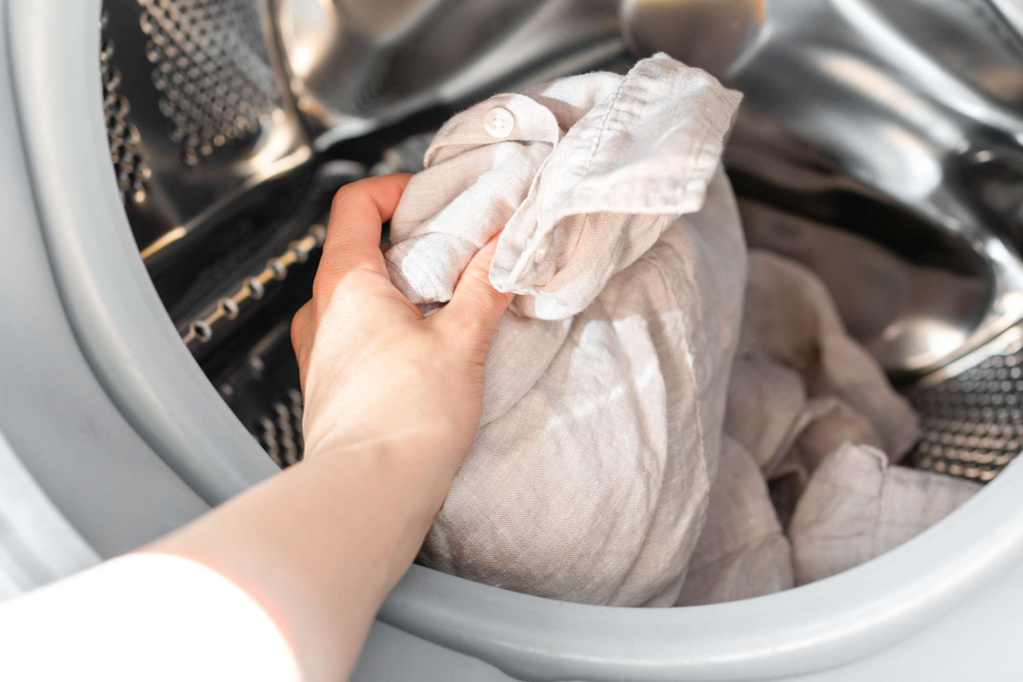 person placing a garment into the washing machine