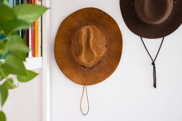 Light and dark brown suede leather hats mounted on white wall next to book shelf