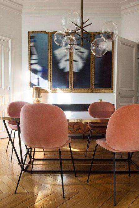 Comedor con arte azul y sillas de color rosa