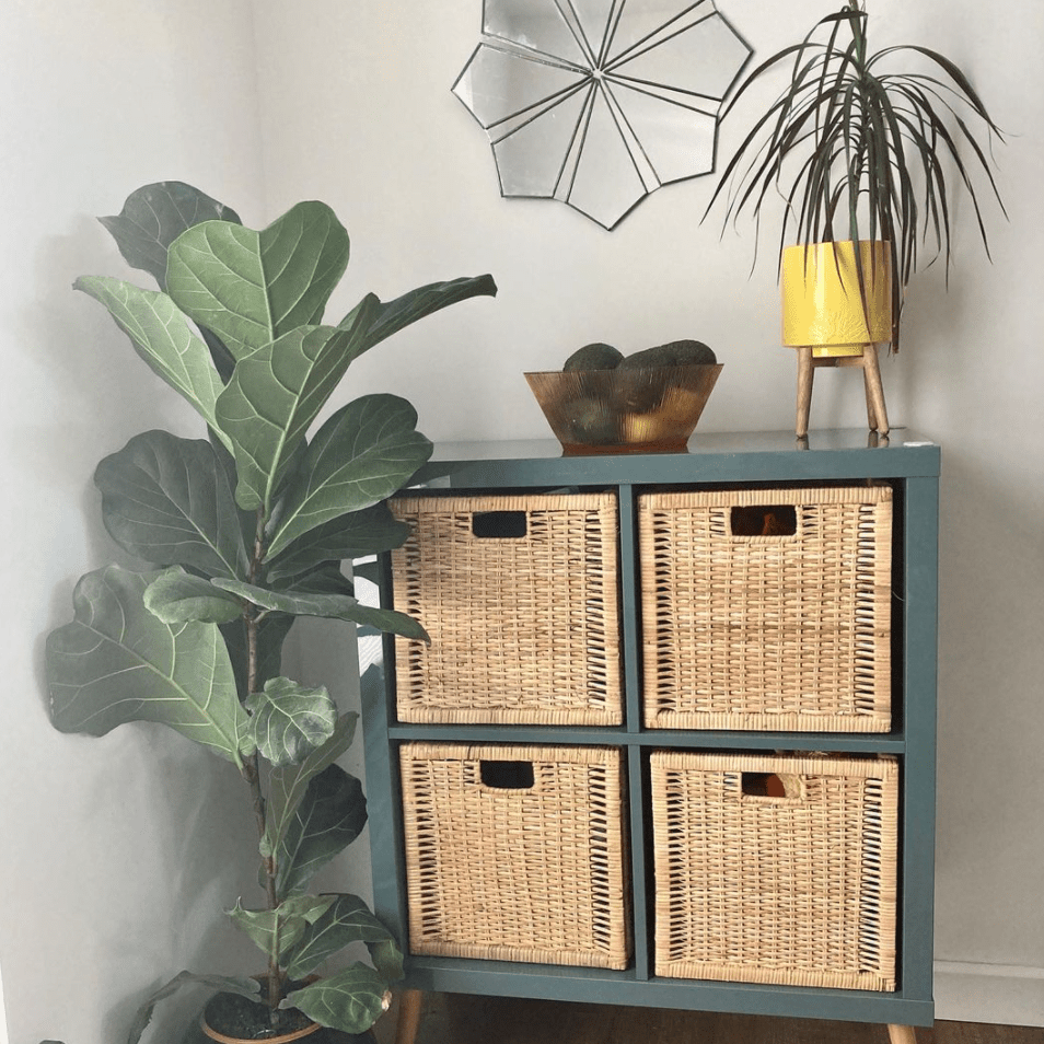 Green storage unit with wooden legs and wicker baskets