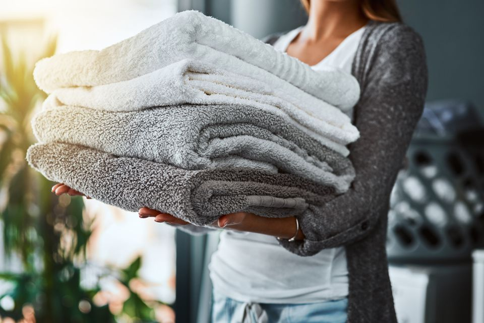 Woman holding fresh and clean towels