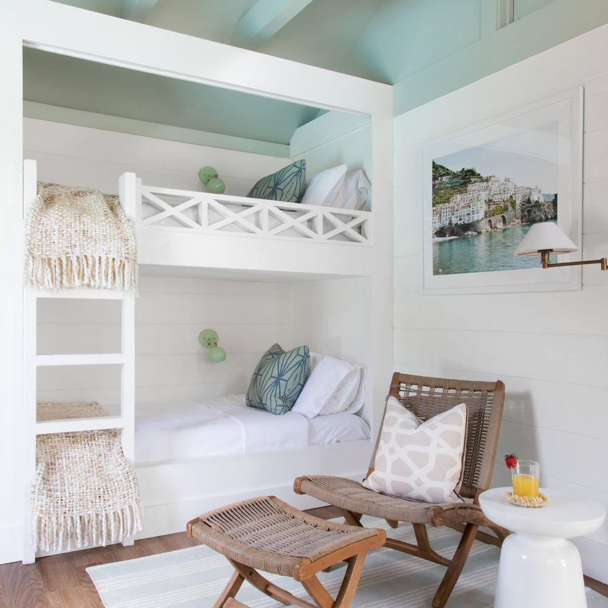 bedroom with bunk beds, teal ceiling with exposed wood beams, white walls, brown and wicker chair with foot stool