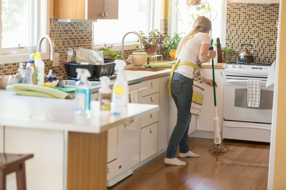 Young woman mopping with green cleaning products
