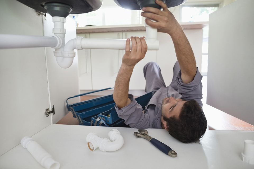 Plumber working on a kitchen sink